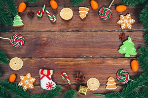 Christmas gingerbread cookies homemade on wooden table with candies, Christmas tree branches and New Year decorations. Xmas frame background