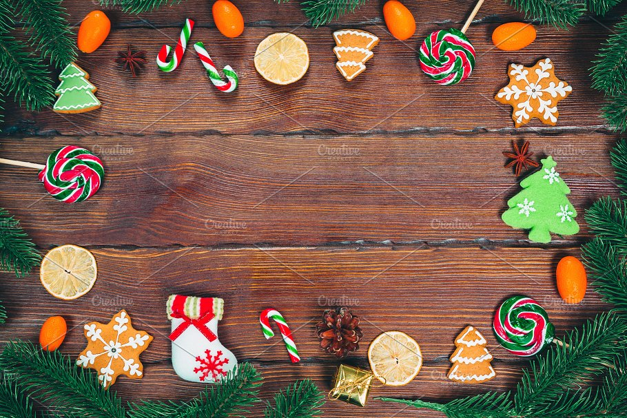 Christmas gingerbread cookies homemade on wooden table with candies, Christmas tree branches and New Year