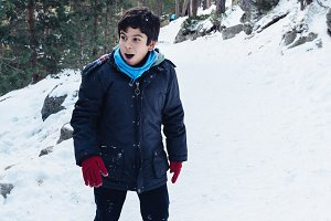 Young boy playing with snowballs