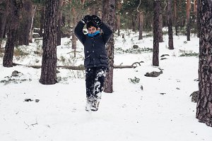Young boy having fun with snow in the mountain