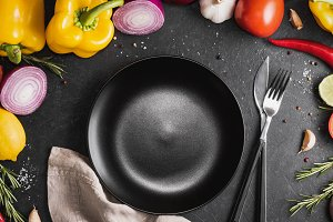 Top view of the empty black plate among fresh vegetables, herbs and spices on the black table. The concept of healthy food.