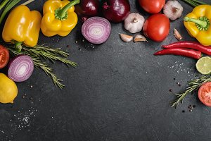 Fresh vegetables, herbs and spices on the black chalkboard. The food background for text.
