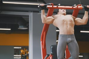 Muscular young athlete man pulling up in a gym, close up