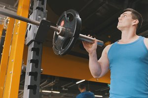 Muscular sporty man add weight for squats mashine in the gym - close up