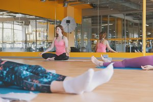 Yoga in the gym - coach shows lotus pose for group of women