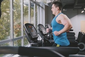 Muscular man in the gym - bodybuilder running on the running track in the gym