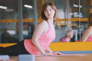 Athletic female shows yoga exercises for women in fitness club