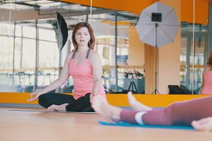 Yoga in fitness centre - athletic female shows exercises for women in fitness club