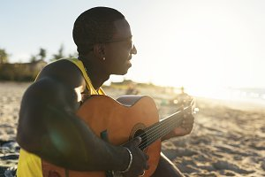 Young cuban man playing the guitar.