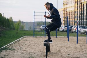 Handsome muscular young man have crossfit training jumping on bar at the park