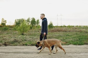 Young sporty man walking with his bullmastiff dog outdoor at nature after crossfit training