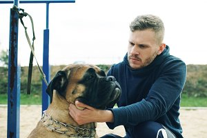 Young sporty man hug and play his bullmastiff dog outdoor at nature