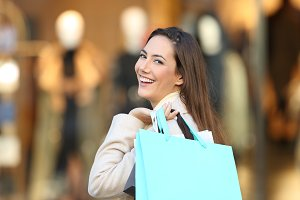 happy shopper holding shopping bags