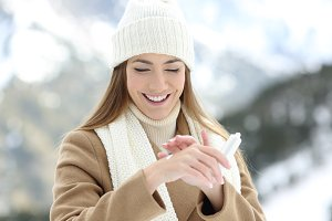 happy woman applying moisturizer
