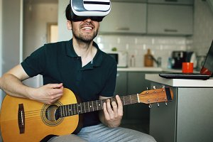 Happy young man sitting at kitchen learning to play guitar using VR 360 headset and feels him guitarist at concert at home