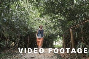 Young girl walks in bamboo alley, Georgia