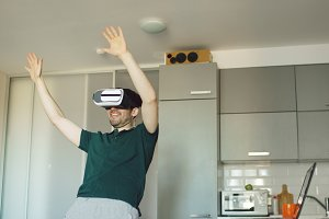 Funny young man in virtual reality 360 headset dancing in kitchen in the morning while listening to music and have fun at home