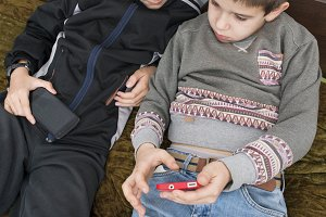Children playing with their smartpho