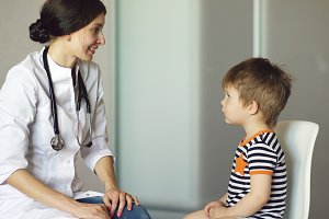 Young woman doctor talking little boy and listening with stethoscope in medical office