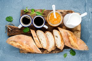 Breakfast set. Baguette, orange jam and coffee in cups