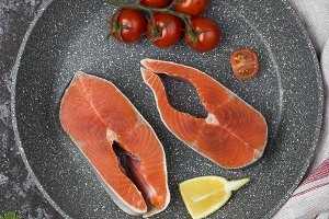 raw salmon steak with herbs, parsley and lemon