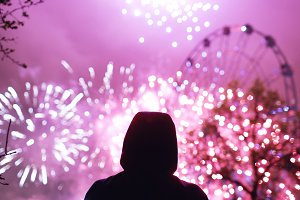 Closeup silhouette of alone man watching fireworks on new year celebration outdoors