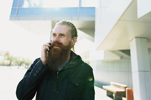 Young bearded hipster man concentrated talking on phone on citystreet, conversation near office building