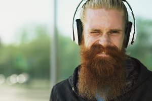 Closeup portrait of young bearded hipster man with headphones listen to music and smiling at city street
