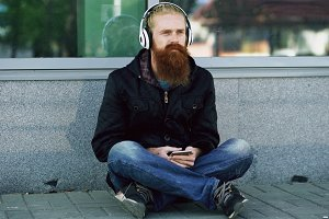 Young bearded hipster man with headphones sitting on road and using smartphone for listen to music and internet surfing outdoors at street