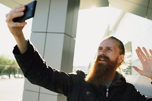 Young bearded hipster man having online video chat with smartphone camera while travel city street