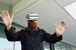 Young bearded man using virtual reality headset for 360 VR experience while walking down city street outdoors