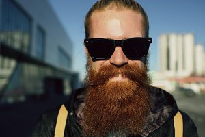 Closeup portrait of young bearded hipster man in sunglasses smiling and posing while travelling city street