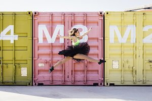 Ballerina with tutu jumping in front of some containers