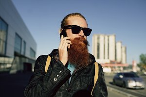 young bearded hipster man in sunglasses smiling and talking smartphone while travelling city street