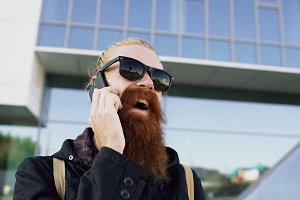 Closeup of Young bearded hipster man in sunglasses smiling and talking smartphone near office buildings