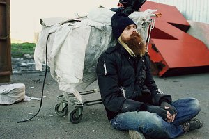 Young bearded homeless man sitting on a sidewalk near shopping cart ang garbage container during cold winter day