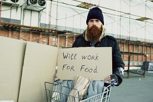 Portrait of young homeless man with cardboard looking at camera and wants to work for food standing near shopping cart