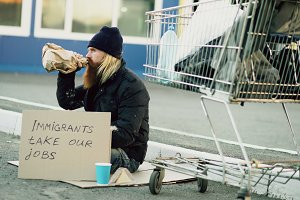 Bearded young homeless man with cardboard sitting near shopping cart and drink alcohol at cold day. Immigrants crisis in Europe
