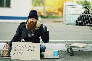 Angry upset young homeless man with cardboard sitting near shopping cart and drink alcohol at cold day because of immigrants crisis in Europe