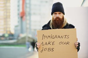 Portrait of young homeless man with cardboard looking at camera and very upset because of immigrants crisis in Europe