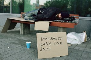 Homeless and jobless european man with cardboard sign sleep on bench at city street because of immigrants crisis in Europe