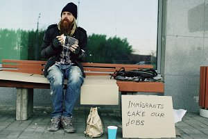 Homeless and jobless european man with cardboard sign eat sandwich on bench at city street because of immigrants crisis in Europe