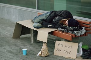 Young homeless drunk man preparing to sleep on cardboard on bench at the sidewalk