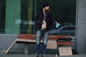 Very drunk homeless man with cardboard and alcohol sign beg for money while standing near bench at the sidewalk