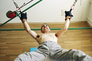 Young man doing exircise on quartering yoga equipment and pull his arms and legs with ropes