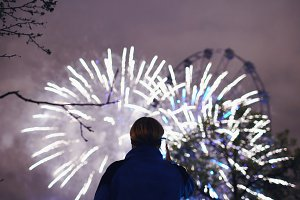 Closeup silhouette of man watching and photographing fireworks explode on smartphone camera outdoors