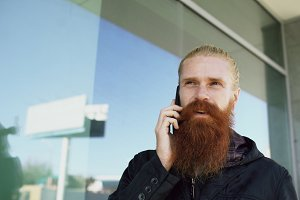 Young bearded hipster man concentrated talking on phone on citystreet and have conversation near office building