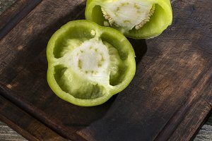 Cut green pepper on wood
