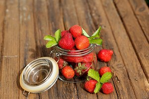 strawberries in a jar on the old wooden background shabby rustic retro style
