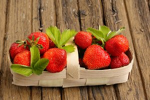 strawberries in a basket on an old shabby wooden background rustic retro style
